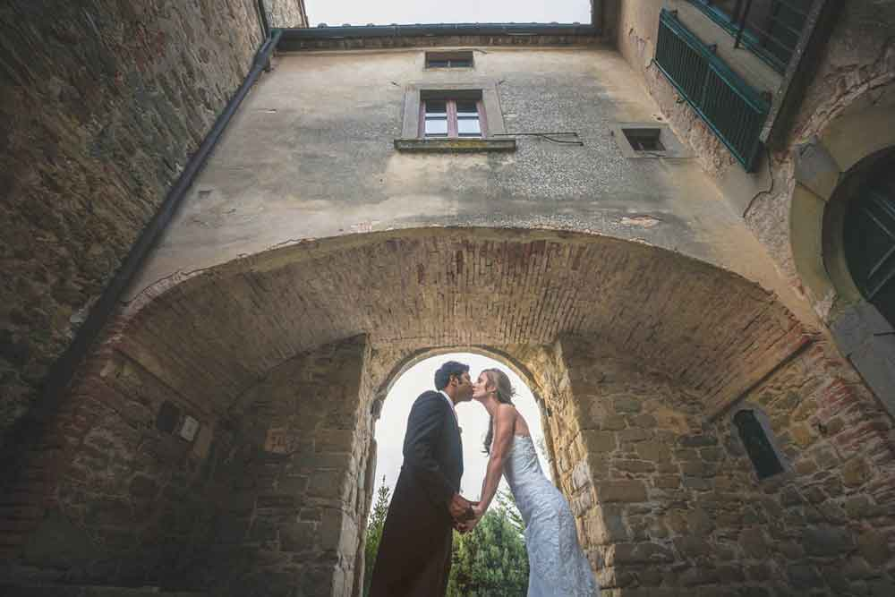 wedding tuscany kiss under the arch